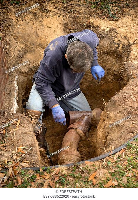 Man in a hole in the earth examining old clay sewer pipes that are infested with tree roots