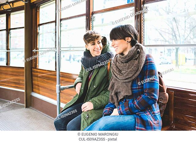Two women sisters sitting on cable car, smiling