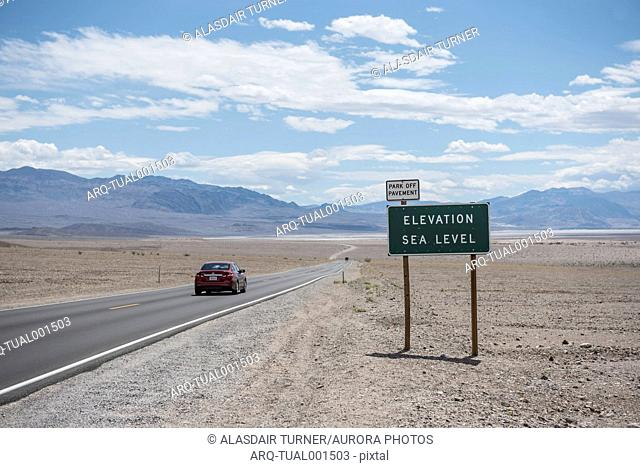 Car driving on road in Death Valley National Park at sea level, California, USA