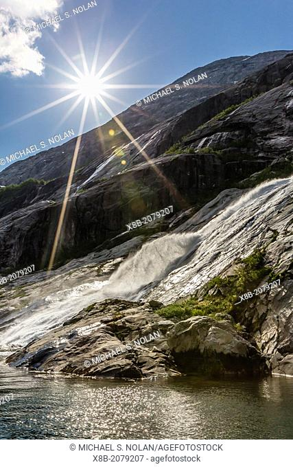 "A roaring waterfall cascading down the mountain side deep in the fjord of Svartisen (""Black Ice† National Park), Nordfjord, Norway"