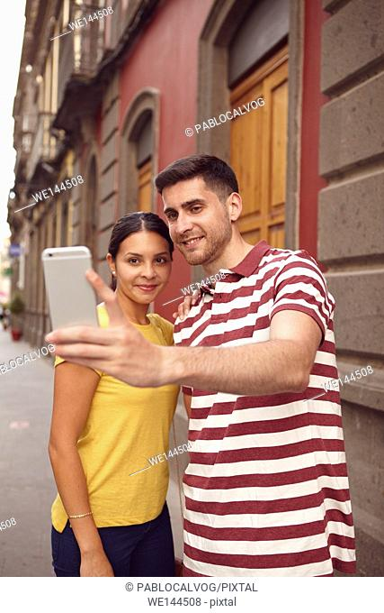 Cute young couple looking at cell phone while smiling happily to take a selfie, dressed casually in t-shirts with old buildings behind them