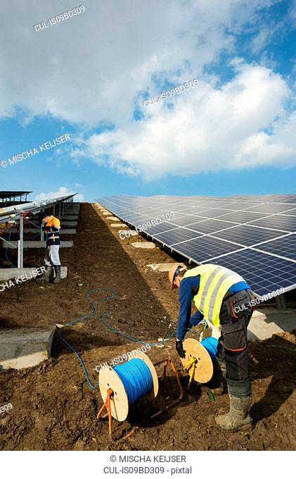 Engineers connecting solar panels on new solar farm, situated on former waste dump
