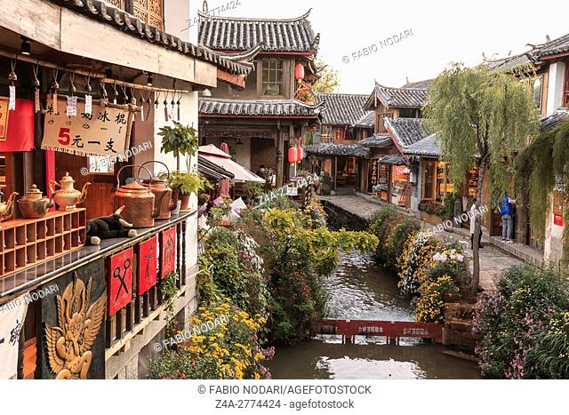 Panoramic view of one of the canals in Lijiang Old Town at sunset with some tourists passing by
