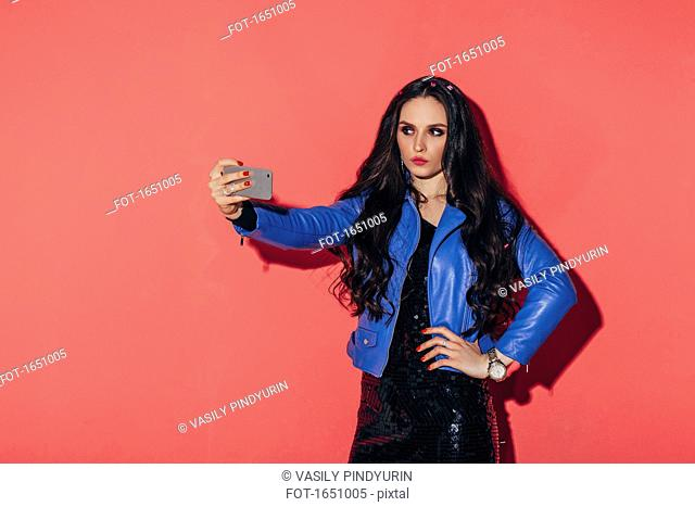 Fashionable woman taking selfie against coral background