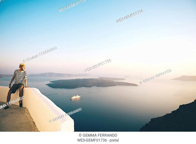 Greece, Santorini, Fira, man on holidays enjoying the sunset over the sea
