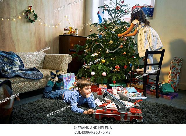 Girl arranging christmas tree whilst brother plays with xmas gifts on sitting room floor
