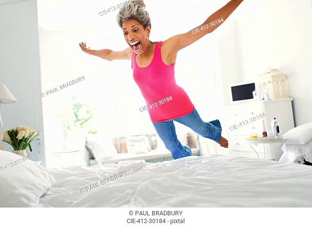 Playful mature woman jumping onto bed