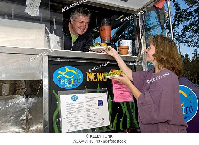 A vendor sells food to a woman from a mobile kitchen in Sechelt, British Columbia, Sunshine coast, Vancouver coast and mountain region, Canada