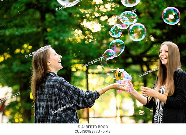 Two young female friends making floating bubbles in park
