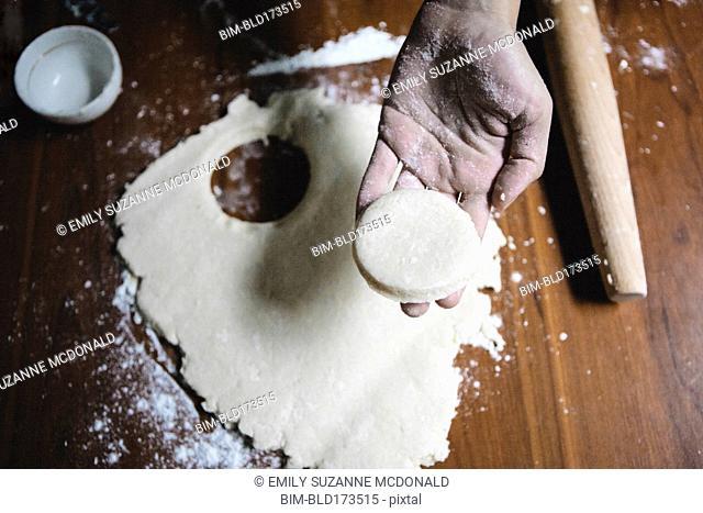 Mixed race baker cutting circle of dough