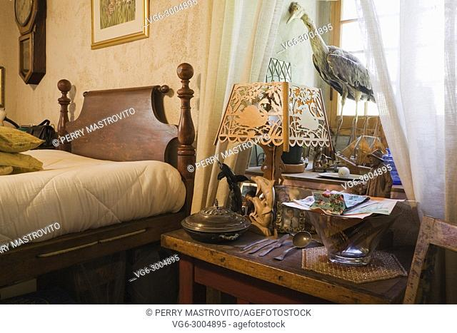 Collectibles displayed on a night table in a bedroom on the upstairs floor inside an old Canadiana (1840s) fieldstone cottage style residential house, Quebec