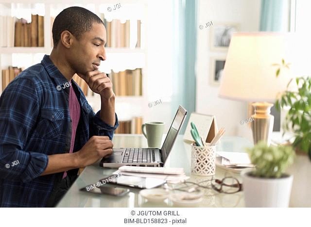 Black businessman working on laptop at desk