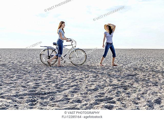 Two girls walking on beach with bike; Toronto, Ontario, Canada