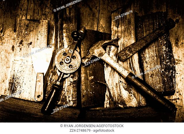High Angle Still Life of Rusty Old Hand Tools - Scraper, Drill, Hammer and Chisel - on Rustic Wooden Surface in Sepia Tone Tinting