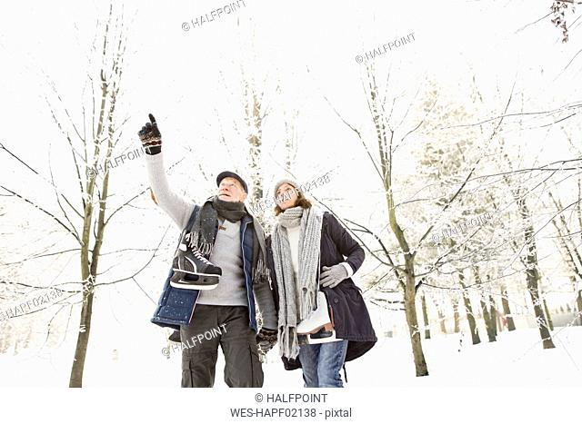 Senior couple with ice skates in winter forest