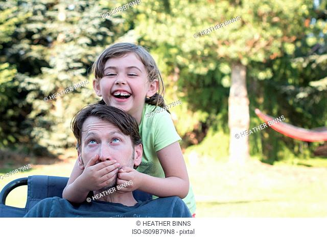 Father and daughter fooling around outdoors, young girl covering father's mouth, laughing