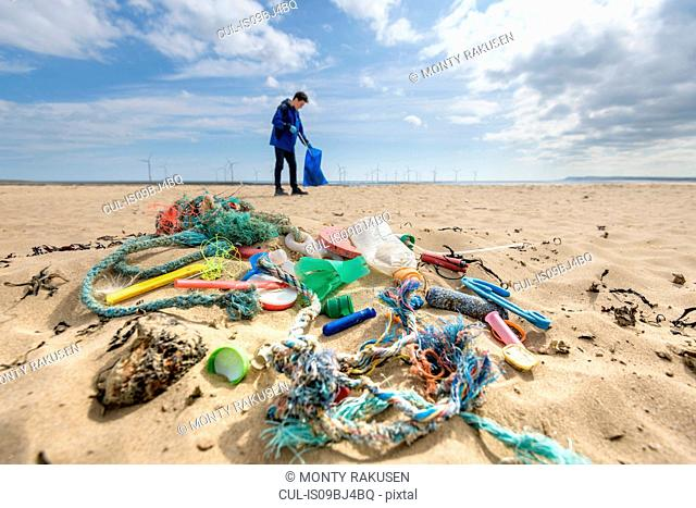 Man picking up plastic pollution collected on beach, North East England, UK