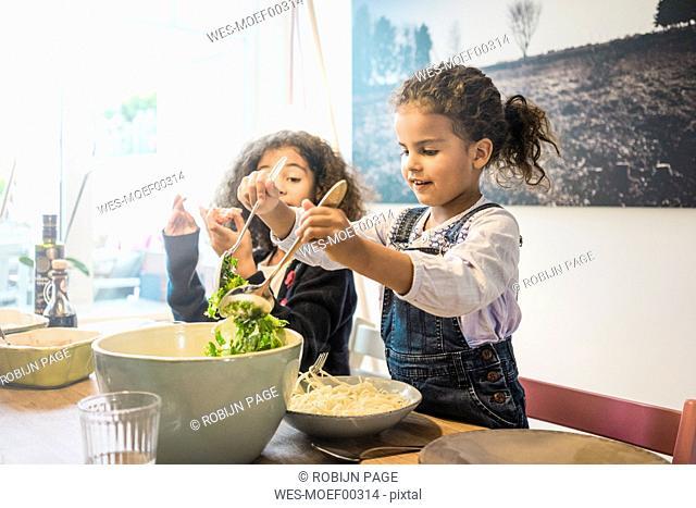 Happy family eating spaghetti, girl serving salad