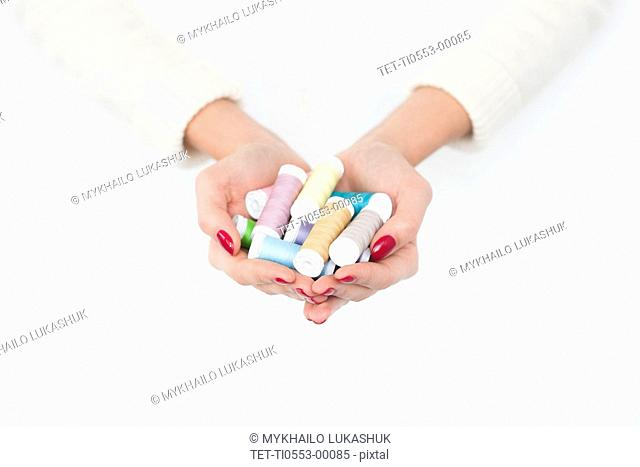 Hands of woman holding spools of cotton