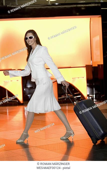 Business woman pulling suitcase, smiling, side view