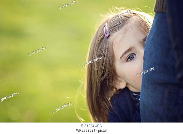 Girl with long brown hair wearing pink hair clip peering at camera