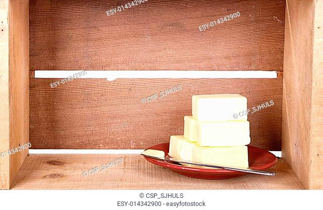 Stacked butter on a plate, wooden background