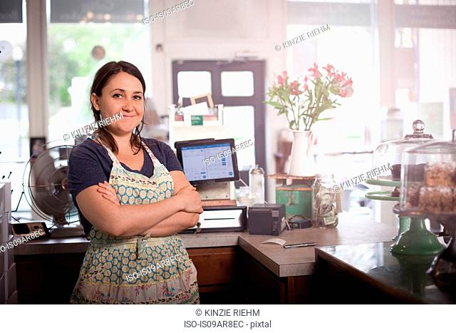 Bakery owner with arms crossed behind counter
