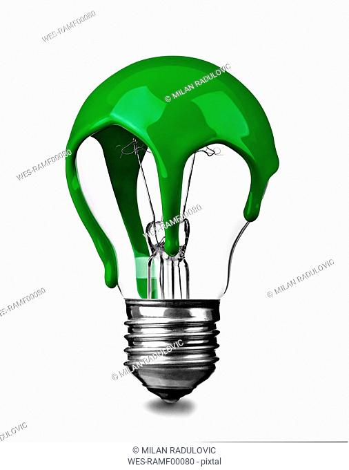 Close up of a green colored light bulb on white background, sustainability concept