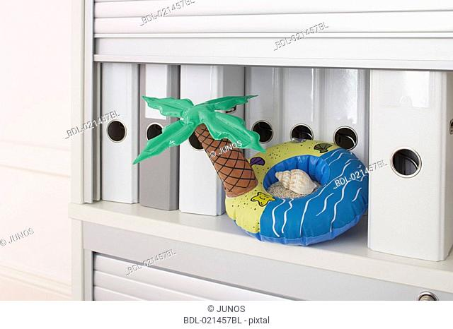 still life of inflatable in form of island in filing cabinet