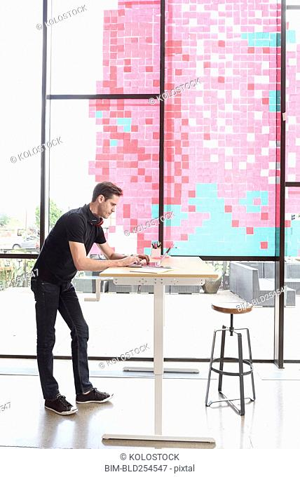 Caucasian man using a laptop at standing workstation