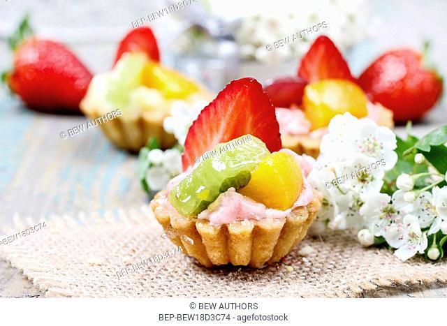 Beautiful cupcakes decorated with fresh fruits: strawberry, peach, kiwi