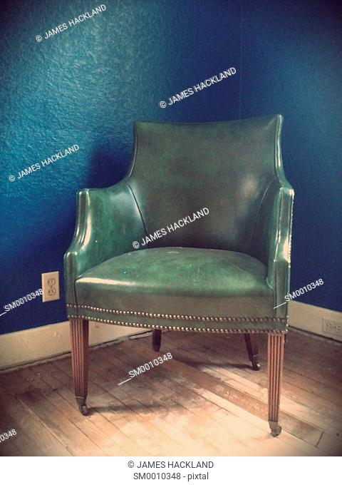 A lonely green chair in front of a blue wall found in an abandoned house near Whitby, Ontario, Canada. There is no property release available but the house no...
