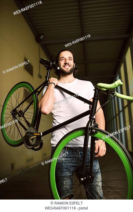 Smiling young man carrying fixie bike