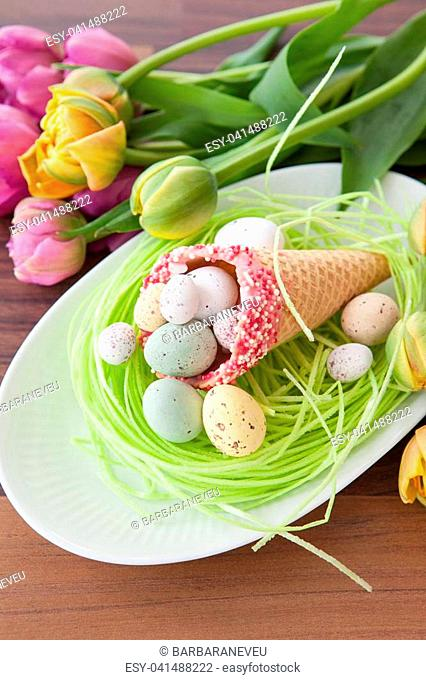 Little easter nest with candy in waffle cones and fresh tulips
