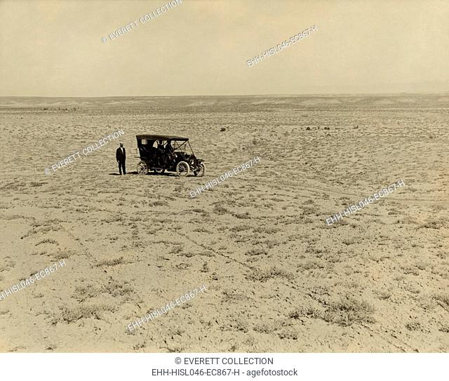 Early automobile parked in an expansive area of barren land in the Grand Valley, Mesa County, Colorado, c. 1912. The land will become part of the Grand Valley...