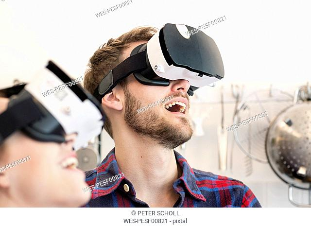Happy young couple wearing VR glasses