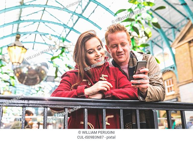 Couple using mobile phone, Covent Garden, London, UK