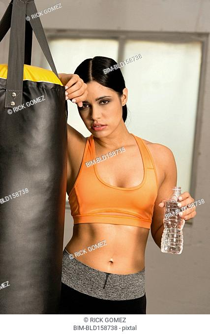 Hispanic athlete resting near punching bag in gymnasium