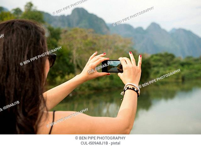 Woman using camera phone, Nam Song River, Vang Vieng, Laos