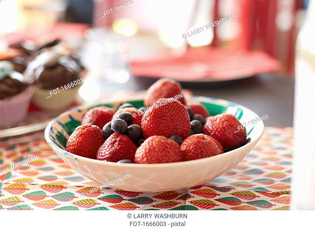 Close-up of fresh berries in bowl on table at home