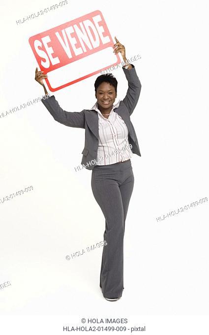 Real Estate agent holding a For Sale Se Vende sign