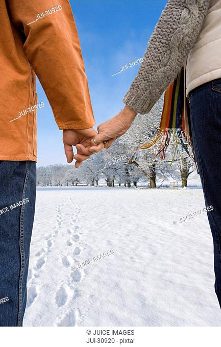 Close up of couple holding hands in snowy field