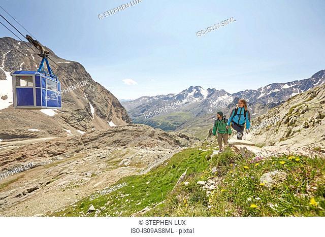 Young hiking couple and cable car at Val Senales Glacier, Val Senales, South Tyrol, Italy