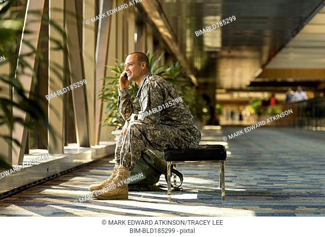 Caucasian soldier talking on cell phone in airport