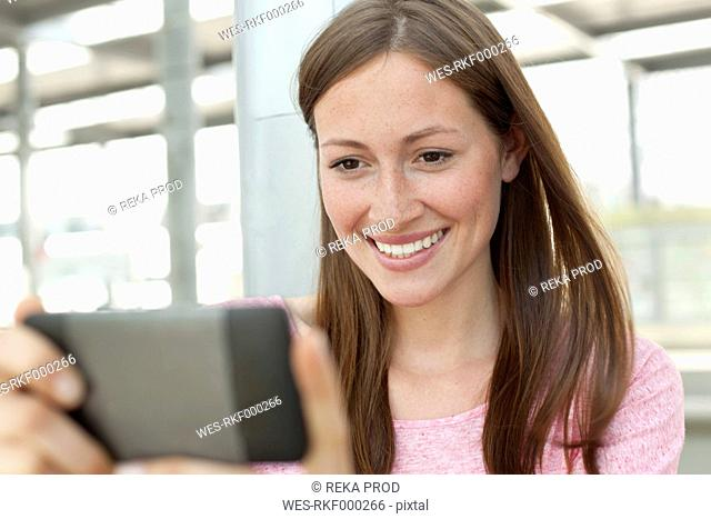 Germany, North-Rhine-westphalia, Duesseldorf, Young woman watching smart phone