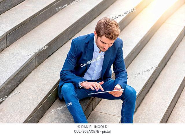 Man sitting on steps looking down using digital tablet