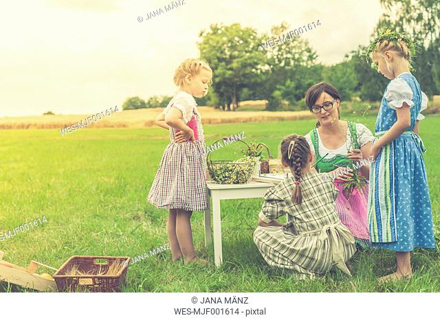 Germany, Saxony, three little girls and their educator in traditonal clothes on a meadow