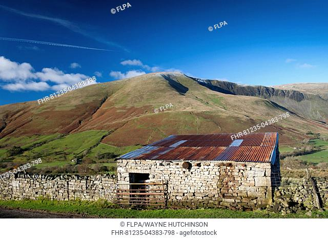View of stone barn and farmland in fell valley, looking from Bluecaster, Cautley Crag, Sedbergh, Howgill Fells, Cumbria, England, November