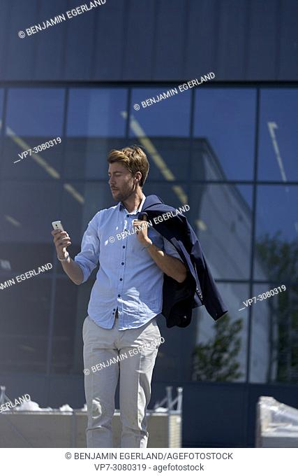 Portrait of Youtuber Axel Sprenger using smartphone in front of glass architecture, wearing business clothes. In Germany, Bavaria