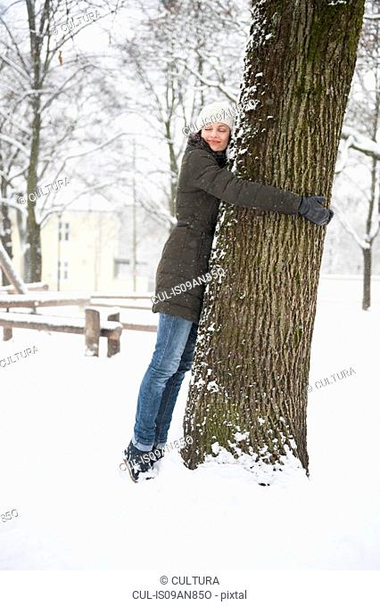 Portrait of mid adult woman, hugging tree, in snow covered rural scene